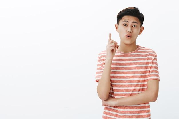 Junger kreativer asiatischer männlicher student, der ideen während des gruppenprojekts teilt, das zeigefinger in der eureka-geste anhebt, um vorschlag hinzuzufügen