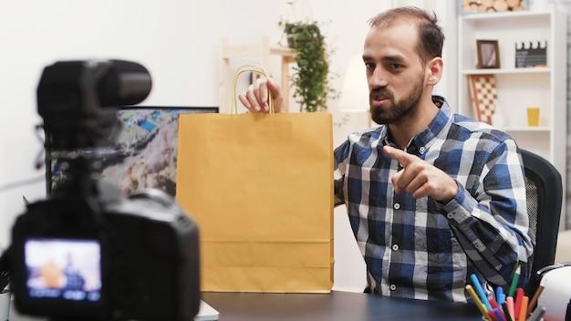 Junger kreativer content-ersteller, der ein werbegeschenk in seinem vlog aufzeichnet. berühmte influencer.