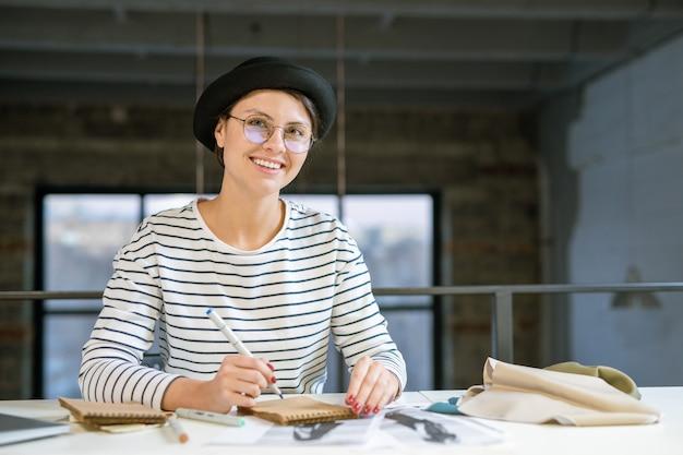 Junger kreativer designer, der durch schreibtisch im studio sitzt und modeskizze zeichnet, während über neue sammlung arbeitet