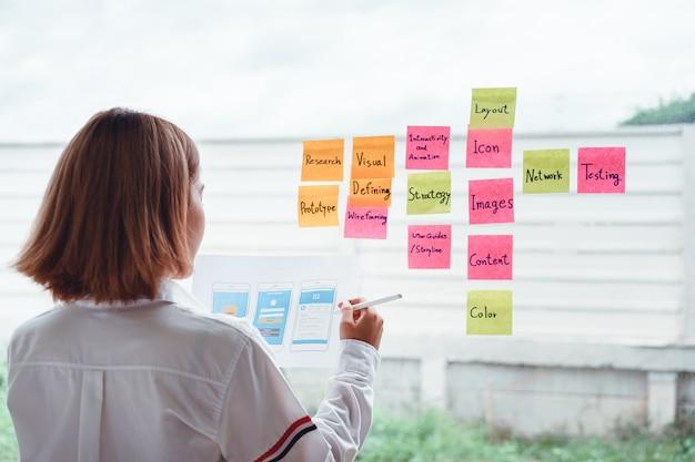 Junger kreativer entwickler der beweglichen anwendung, der mit bunten klebrigen anmerkungen mit sachen arbeitet, um auf der büroglaswand zu tun. user experience-konzept