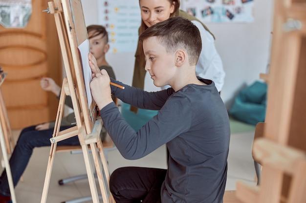 Junger kreativer glücklicher junge zeichnet ein bild, während lehrer ihm hilft