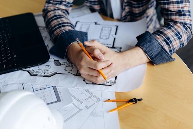 Junger kreativer männlicher ingenieur, der mit neuem projekt auf zeichnung arbeitet