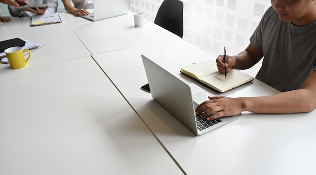 Junger kreativer mann, der laptop-computer im konferenzzimmer verwendet