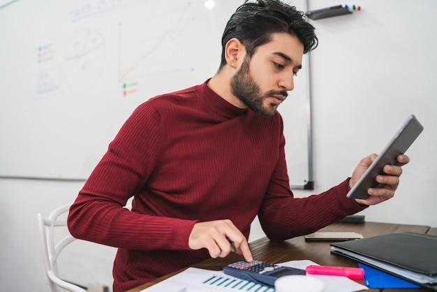 Junger kreativer mann, der mit seinem digitalen tablett arbeitet