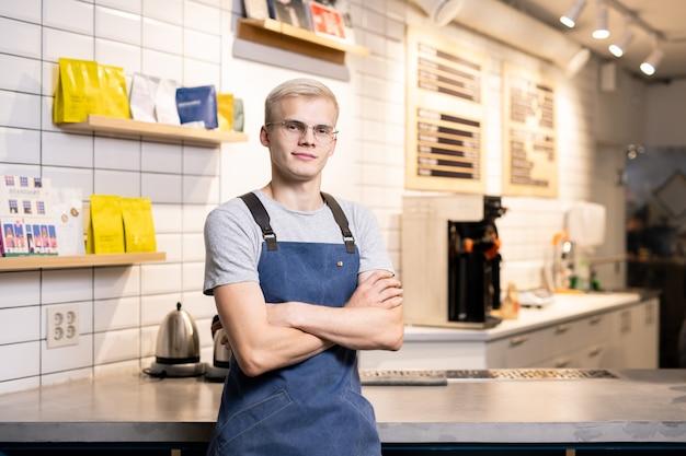 Junger kreuzbewaffneter barista oder besitzer der cafeteria, der am tisch auf hintergrund der arbeitsausrüstung und der packungen mit kaffee steht