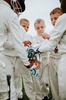 Junger kricketspieler, der zusammen ihre hände stapelt