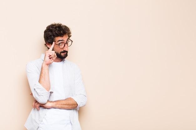 Junger kühler bärtiger mann denkt oder zweifelt an ausdruck