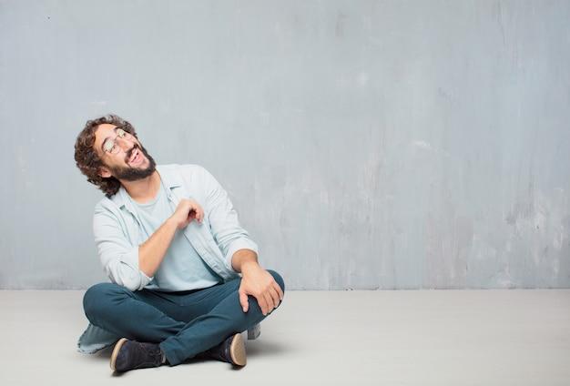 Junger kühler bärtiger mann, der auf dem boden sitzt. grunge wand hintergrund
