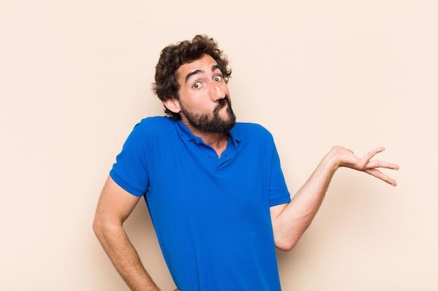Junger kühler bärtiger mann, der denkt oder verwirrt