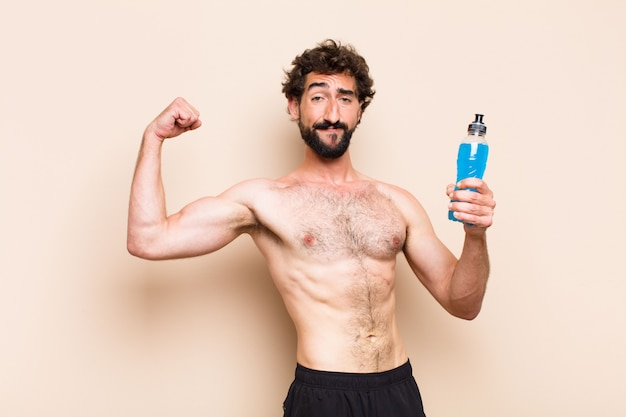 Junger kühler bärtiger mann, der ein energiegetränk-eignungskonzept trinkt