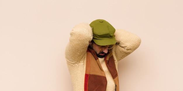 Junger kühler bärtiger mann, der sich gestresst, unglücklich und frustriert fühlt, die stirn berührt und unter migräne mit starken kopfschmerzen leidet