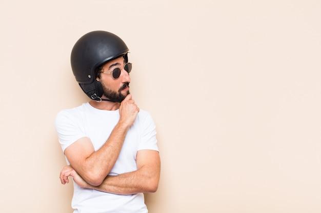 Junger kühler bärtiger mann mit einem denkenden helm