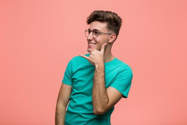 Junger kühler kaukasischer mann, der eine handy-anrufgeste mit den fingern zeigt.