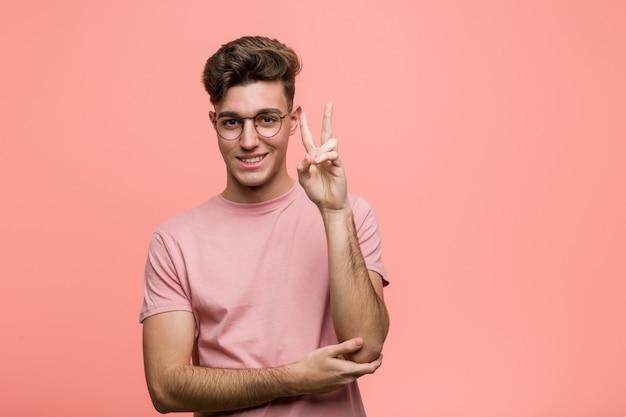 Junger kühler kaukasischer mann, der nummer zwei mit den fingern zeigt.