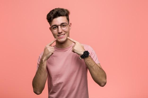 Junger kühler kaukasischer mann lächelt und zeigt finger auf mund.