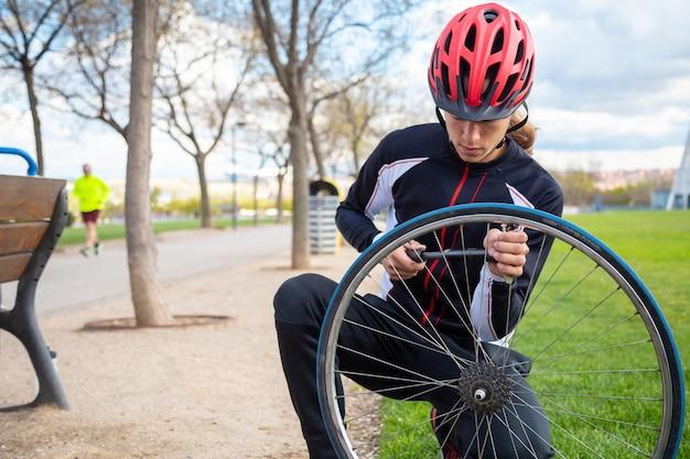Junger kühler männlicher radfahrer in der sportkleidung und in schutzhelm, die luftkammer des fahrrades reparieren, drehen herein park