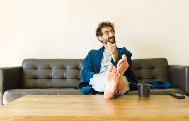 Junger kühler mann, der auf einem sofa am wohnzimmer sitzt und fernsieht