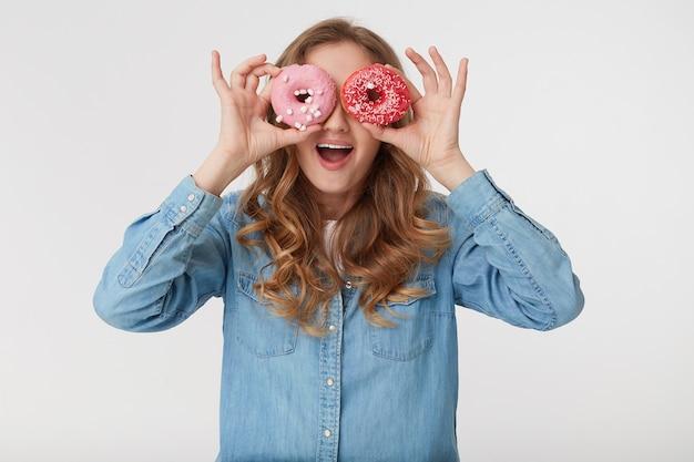 Junger kühler mann, der ein jeanshemd trägt, mit dem langen blonden gewellten haar, das durch donuts schaut und breit lächelt, lokalisiert über weißem hintergrund.