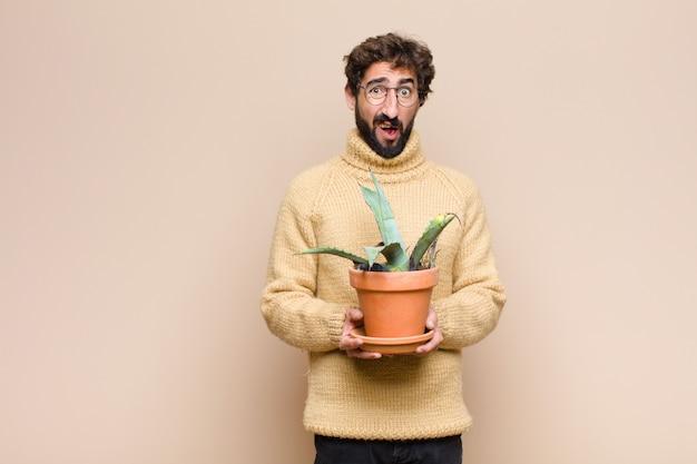 Junger kühler mann, der eine kaktuspflanze an der wand hält