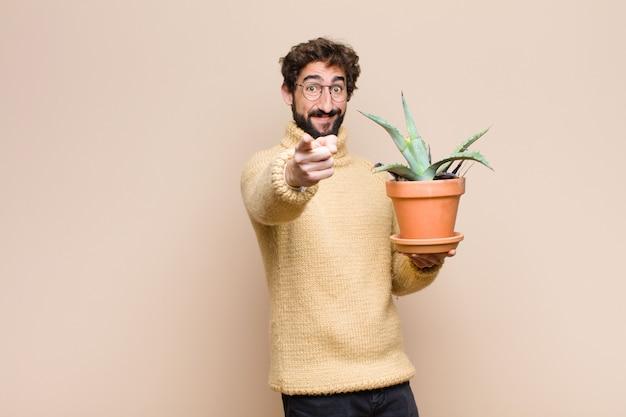Junger kühler mann, der eine kaktuspflanze gegen flache wand hält