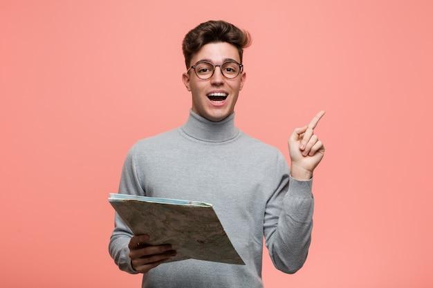 Junger kühler mann, der eine karte zeigt mit dem finger auf sie hält, als ob einladung näher kommen.