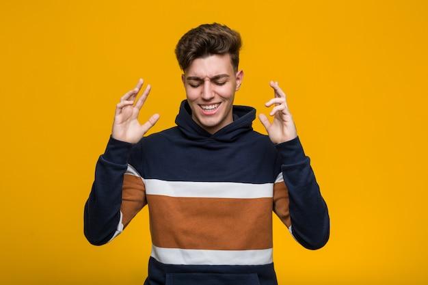 Junger kühler mann, der einen hoodie froh trägt, viel zu lachen. glück-konzept.