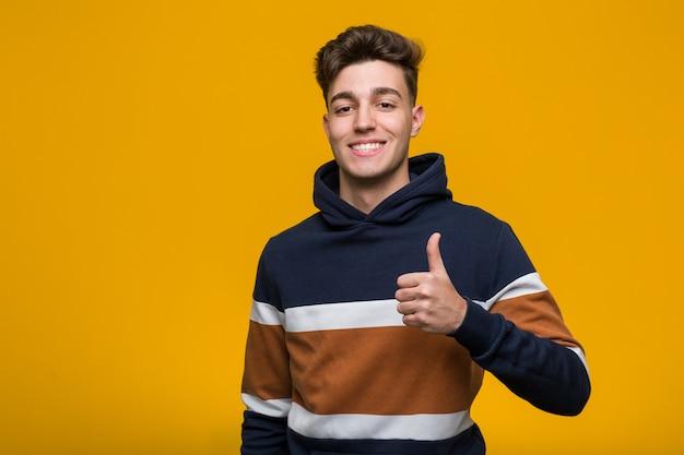 Junger kühler mann, der einen hoodie lächelt und oben daumen anhebt trägt