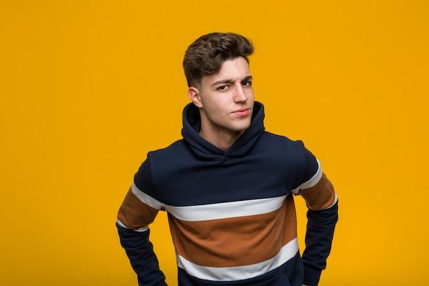 Junger kühler mann, der einen hoodie schilt jemand trägt, das sehr verärgert ist.