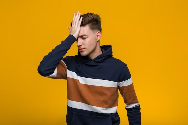 Junger kühler mann, der einen hoodie vergisst etwas trägt, stirn mit palme schlägt und augen schließt.