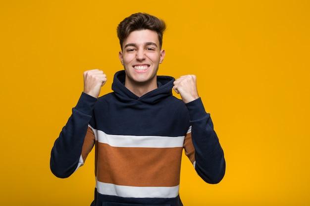 Junger kühler mann, der einen hoodie zujubelt sorglos und aufgeregt trägt. sieg-konzept.