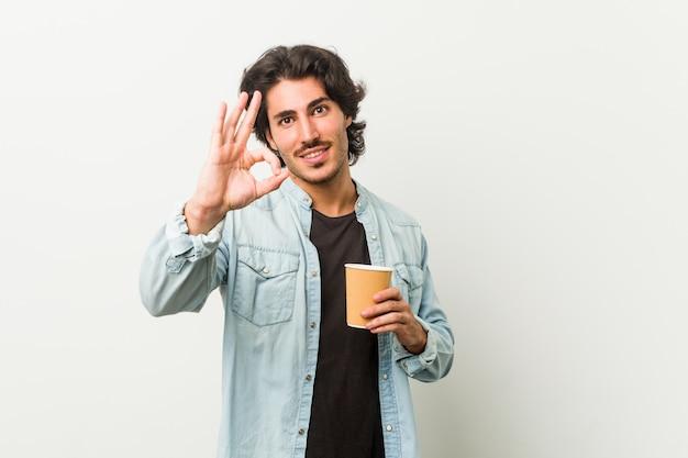 Junger kühler mann, der einen kaffee nett und überzeugt trinkt, okaygeste zeigend.