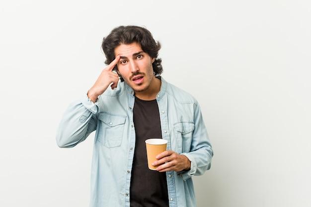 Junger kühler mann, der einen kaffee trinkt, der eine enttäuschungsgeste mit zeigefinger zeigt.
