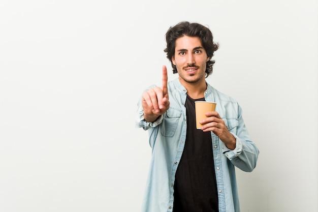 Junger kühler mann, der einen kaffee trinkt, der nummer eins mit finger zeigt.