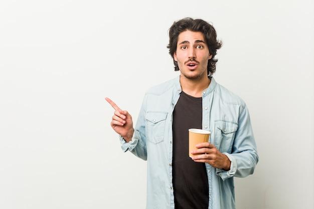 Junger kühler mann, der einen kaffee trinkt, der zur seite zeigt