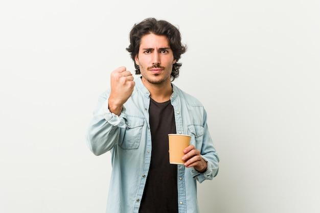 Junger kühler mann, der einen kaffee zeigt faust zur kamera, aggressiver gesichtsausdruck trinkt.