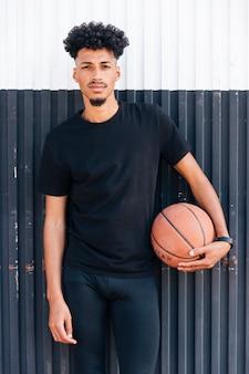 Junger kühler mann, der gegen die wand hält basketball steht