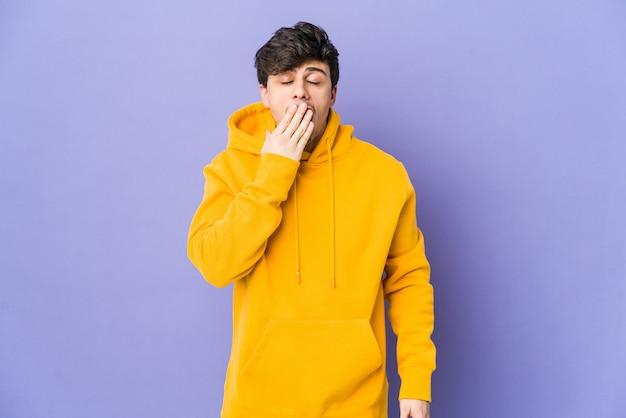 Junger kühler mann gähnt, der eine müde geste zeigt, die mund mit hand bedeckt.