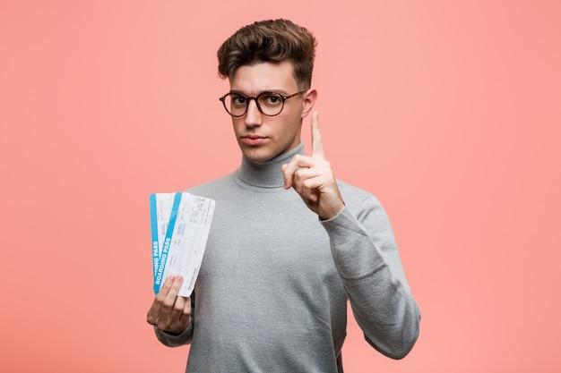 Junger kühler mann, halten flugtickets, die nummer eins mit dem finger zeigen.