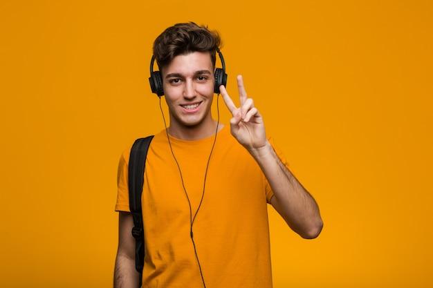Junger kühler studentenmann, der musik mit den kopfhörern haben etwas großartige idee hört