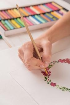 Junger künstler, der blumenmuster mit aquarellfarbe und pinsel am arbeitsplatz zeichnet