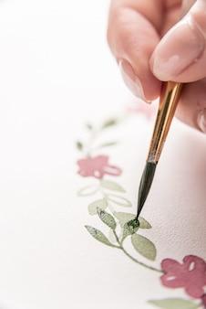 Junger künstler, der blumenmuster mit aquarellfarbe und pinsel auf papier am arbeitsplatz zeichnet