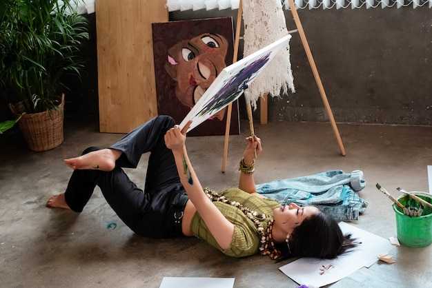Junger künstler, der im erdgeschoss niederlegt und kunstmalereiausbildung an ihrer studiomalereikunst erledigt