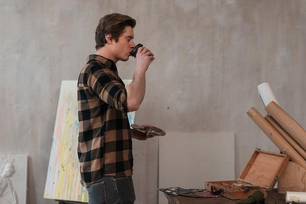 Junger künstler, der seinen kaffee trinkt