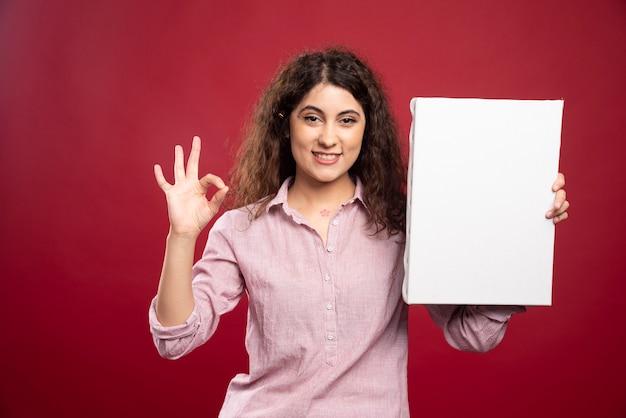Junger künstler mit leerer leinwand, die ok zeichen tut.
