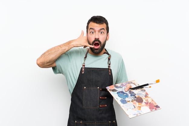Junger künstlermann, der eine palette über dem lokalisierten hintergrund macht telefongeste und das zweifeln hält