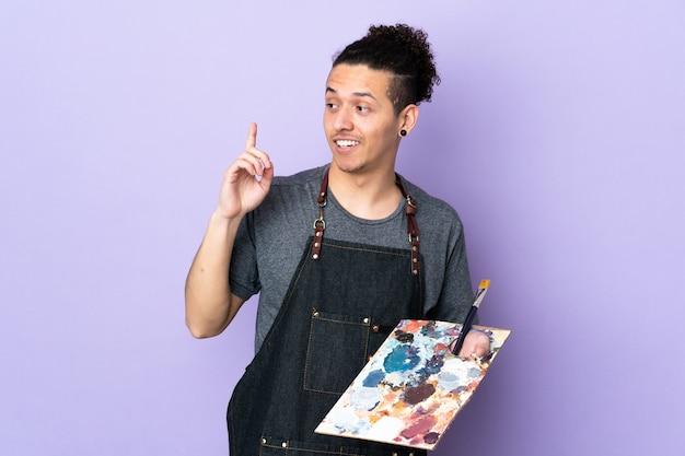 Junger künstlermann, der eine palette über isoliertem lila hintergrund hält, der beabsichtigt, die lösung zu realisieren, während ein finger anhebt
