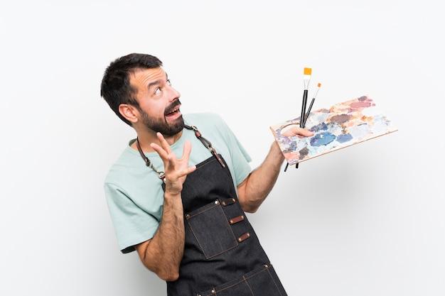 Junger künstlermann, der eine palette über lokalisiertem hintergrund nervös und erschrocken hält