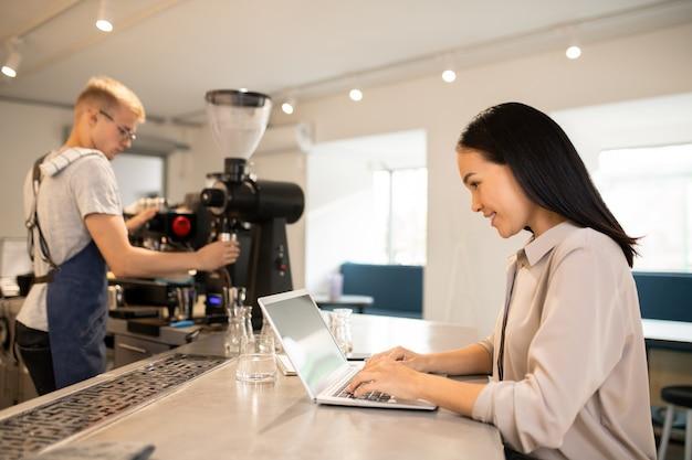 Junger kunde der cafeteria, die durch tisch sitzt und im netz surft, während barista frischen kaffee auf hintergrund vorbereitet