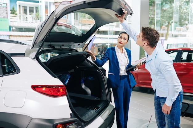 Junger kunde, der das kofferraumschloss des autos überprüft, das er kaufen wird