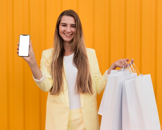 Junger kunde, der gelbe kleidung trägt und ein telefon hält